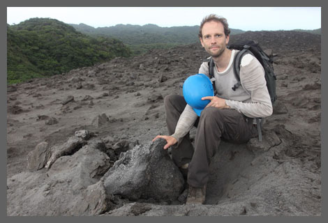 Richard sitting by volcanic bomb crater on Yasur volcano