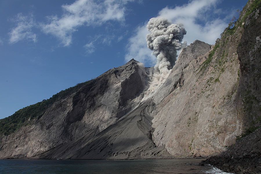 Sea and flank of Komba Island with eruption from active crater of Batu Tara volcano